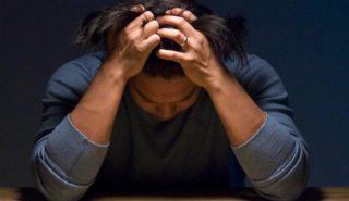 Image of a woman with anxiety holding her head