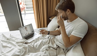sick man in telehealth conference with doctor