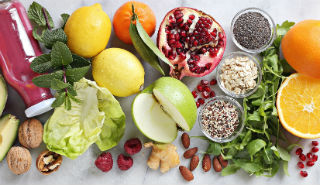Fruits, veggies, nuts and seeds on a white background