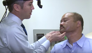 Dr. Coffey examining patient for head and neck cancer.