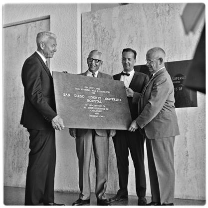 men holding transfer ceremony plaque