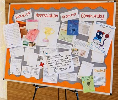 bulletin board full of letters and drawings from the community