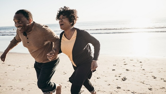 black family laughing, exercising on beach